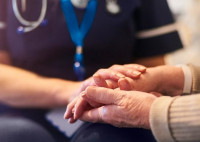 Elderly person with hands held by health professional