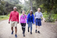 4 older people, two women and two men, are walking on a trail in the forest