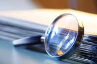 A metal magnifying glass leans against a stack of papers