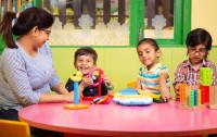 Preschool children learning toy blocks from teacher