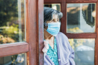 an elderly woman stands in a doorway looking out and is wearing a mask