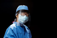 A female frontline worker wears PPE including cap, face shield, mask and gown
