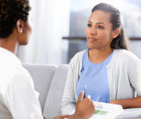 a black woman sits on a couch and talks with another black woman therapist