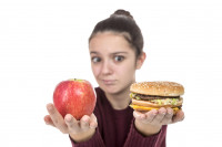 A child holds up an apple and a hamburger with a quizzical expression on her face