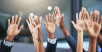Image of raised hands of various ethnicities