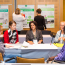A group of people sit at a table and collaborate over a poster during a workshop