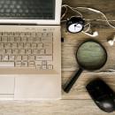 Image of a laptop computer, mouse, headphones, clock