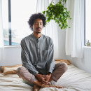 Young man meditating alone in his bedroom at home stock photo
