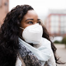 A black woman wears a mask while walking on the street