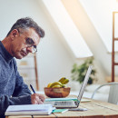 An older man of color works on a laptop and writes in a notebook on a kitchen table