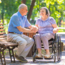 An elderly couple sit in a park, one person in a wheelchair, the other on a bench
